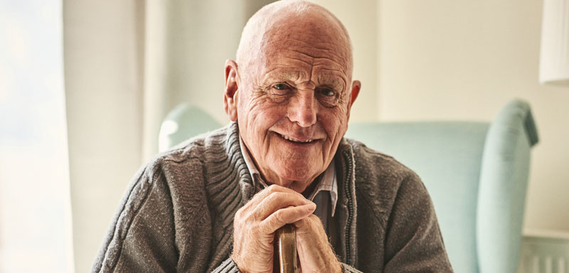 A smiling assisted living male resident in a sweater sitting in chair leaning on his cane