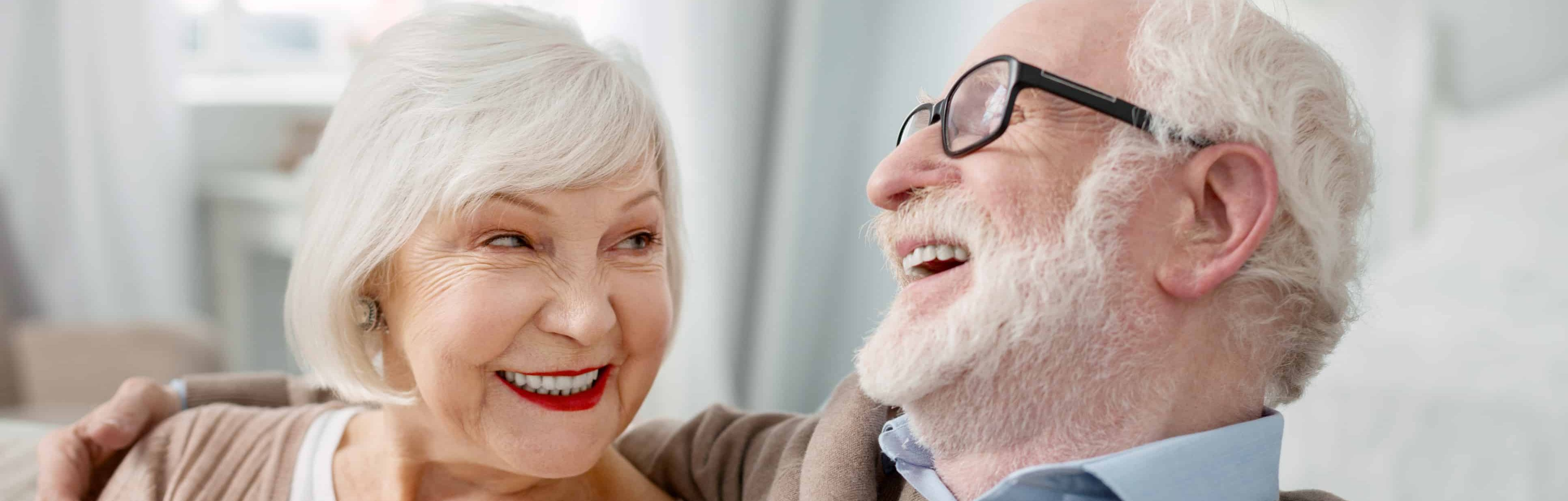 Cheerful elderly man hugging his wife