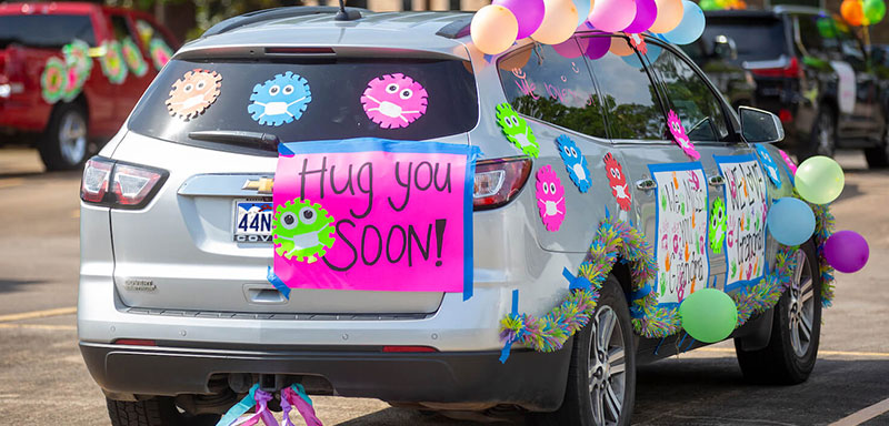 """An SUV with colorful balloons, rainbow feather boas along the edge of the SUV and colorful signs that reads """"Hug You Soon!"""""""