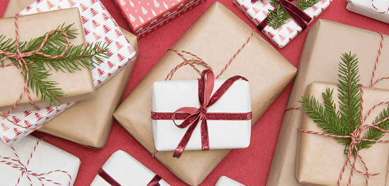 An assortment of wrapped gifts on a red background