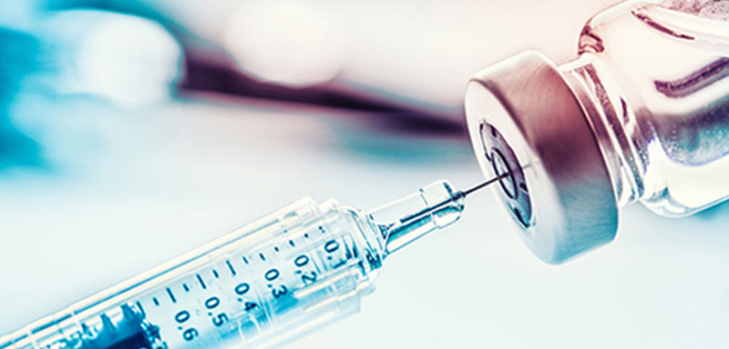 A closeup of a syringe in a vaccine vial