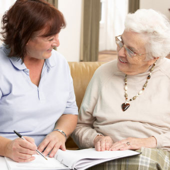 A female home health caregiver with a notebook talking with a female resident sitting on a couch