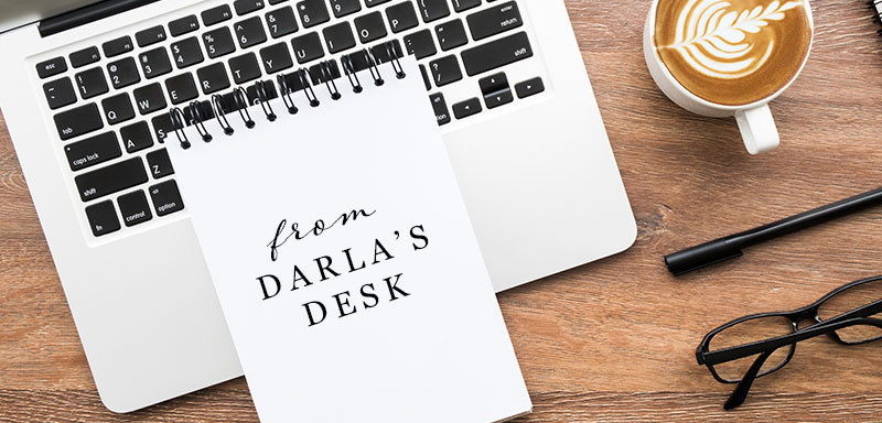 A top down view of a notebook on a laptop that has From Darla's Desk written on it next to a coffee,pen and glasses on a wooden desk.