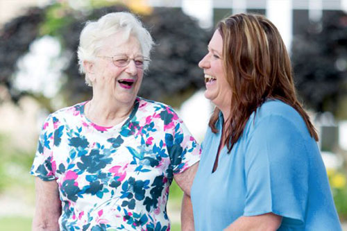 Female employee wearing blue walking with an assisted living female resident wearing a floral shirt. They are talking and laughing
