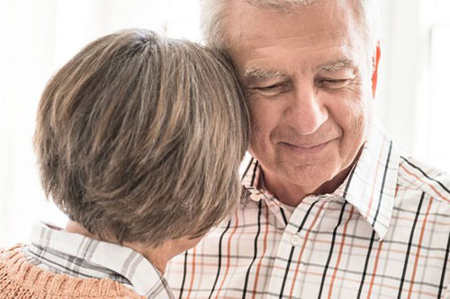 A senior male wearing a plaid shirt in enhanced assisted living getting a hug from his wife