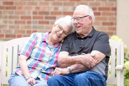 An elderly woman laying her head on an elderly mans shoulder on a bench
