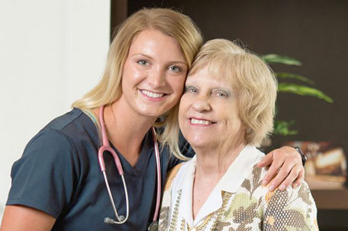 A smiling female nurse with her arm around a female memory care resident