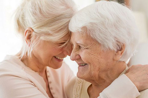 A smiling middle age daughter with her head against her smiling mother who needs respite care