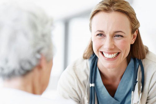 A close up of a smiling nurse talking with a female skilled nursing resident in a wheel chair with a white blurred background