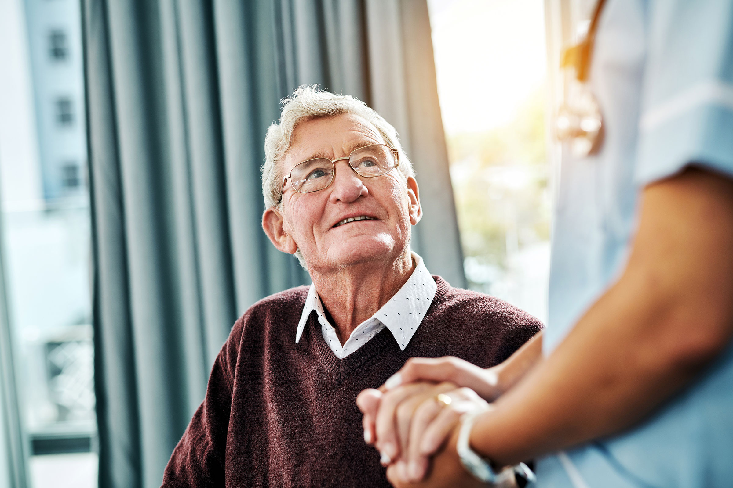 A senior male resident in a maroon sweater holding hands with caretaker in long term care