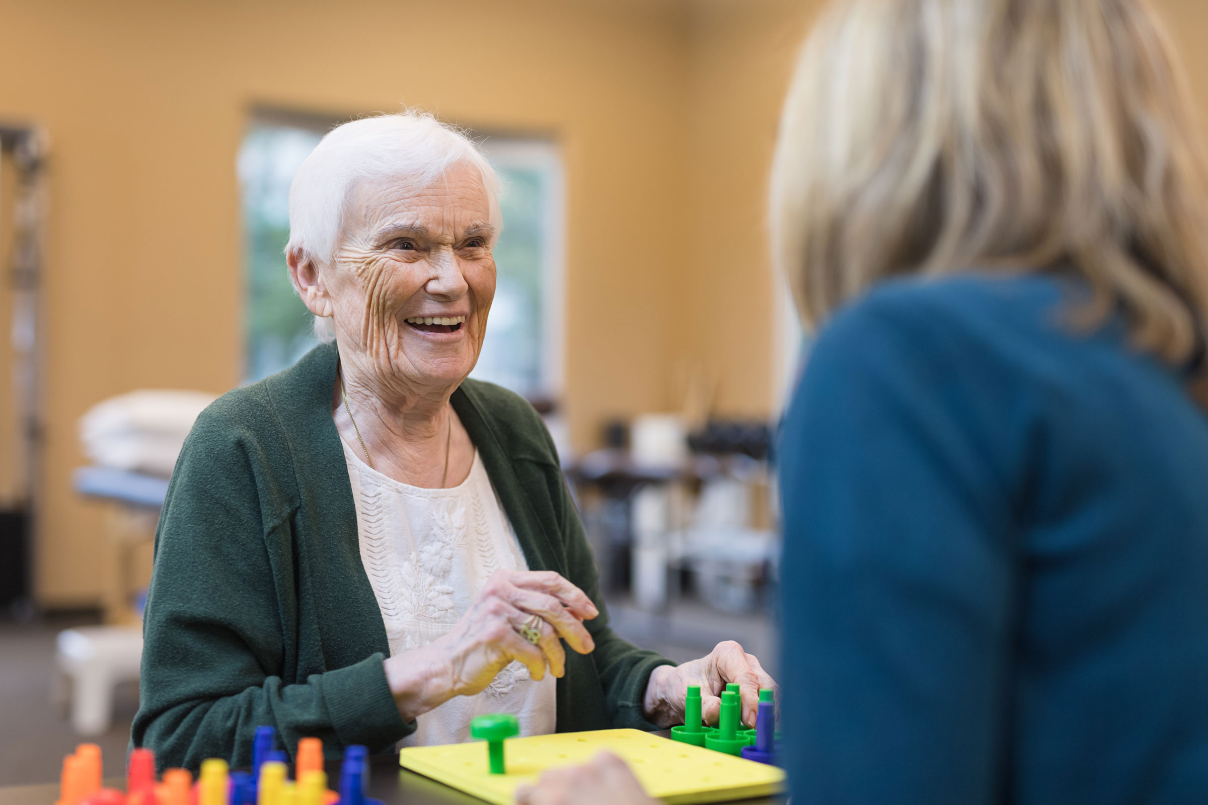 A senior smiling female doing occupational therapy by placing pegs into a board while looking at a female therapist dressed in blue