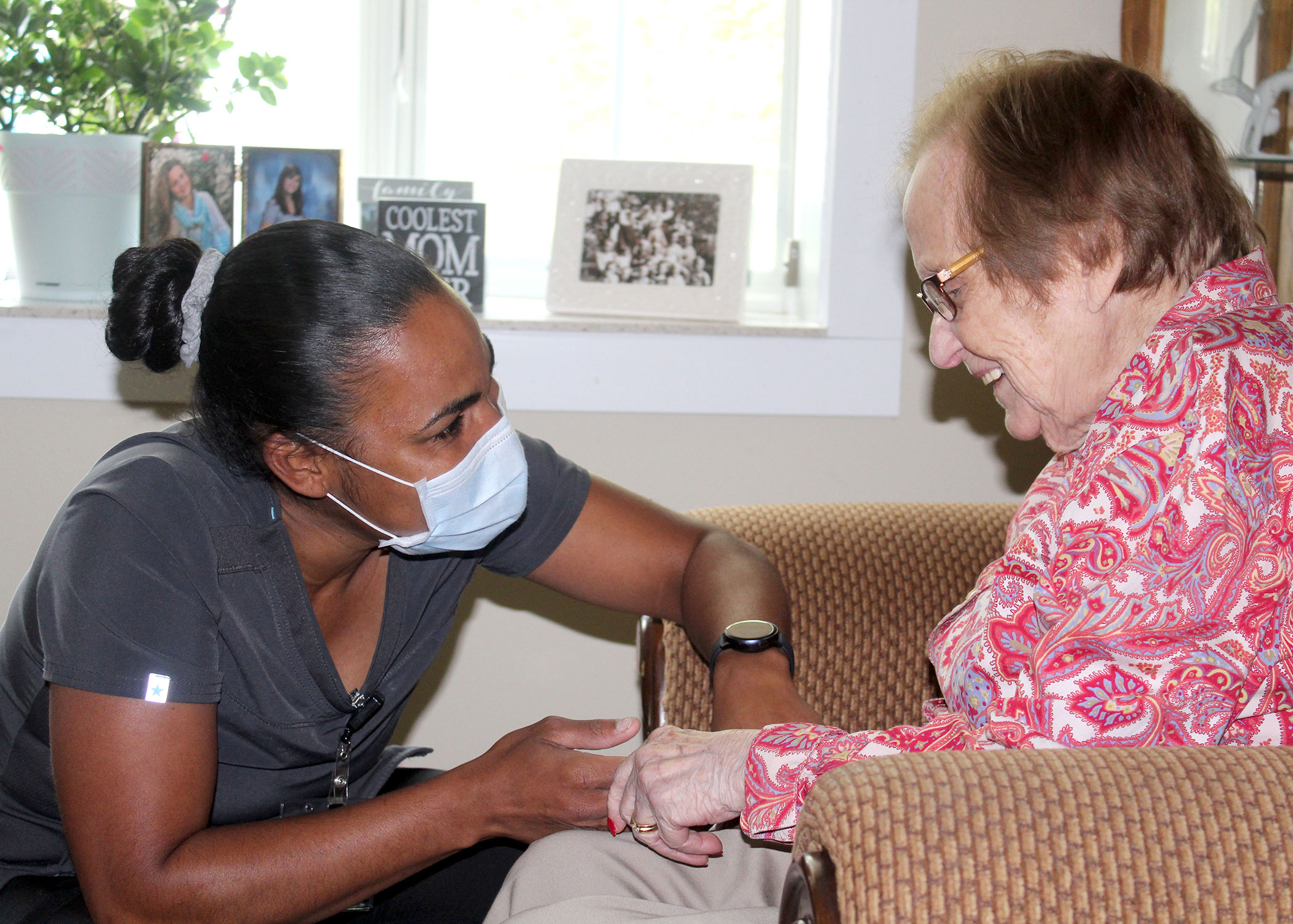 Female CNA with face mask holds the hand of a female memory care resident who is smiling with a red shirt