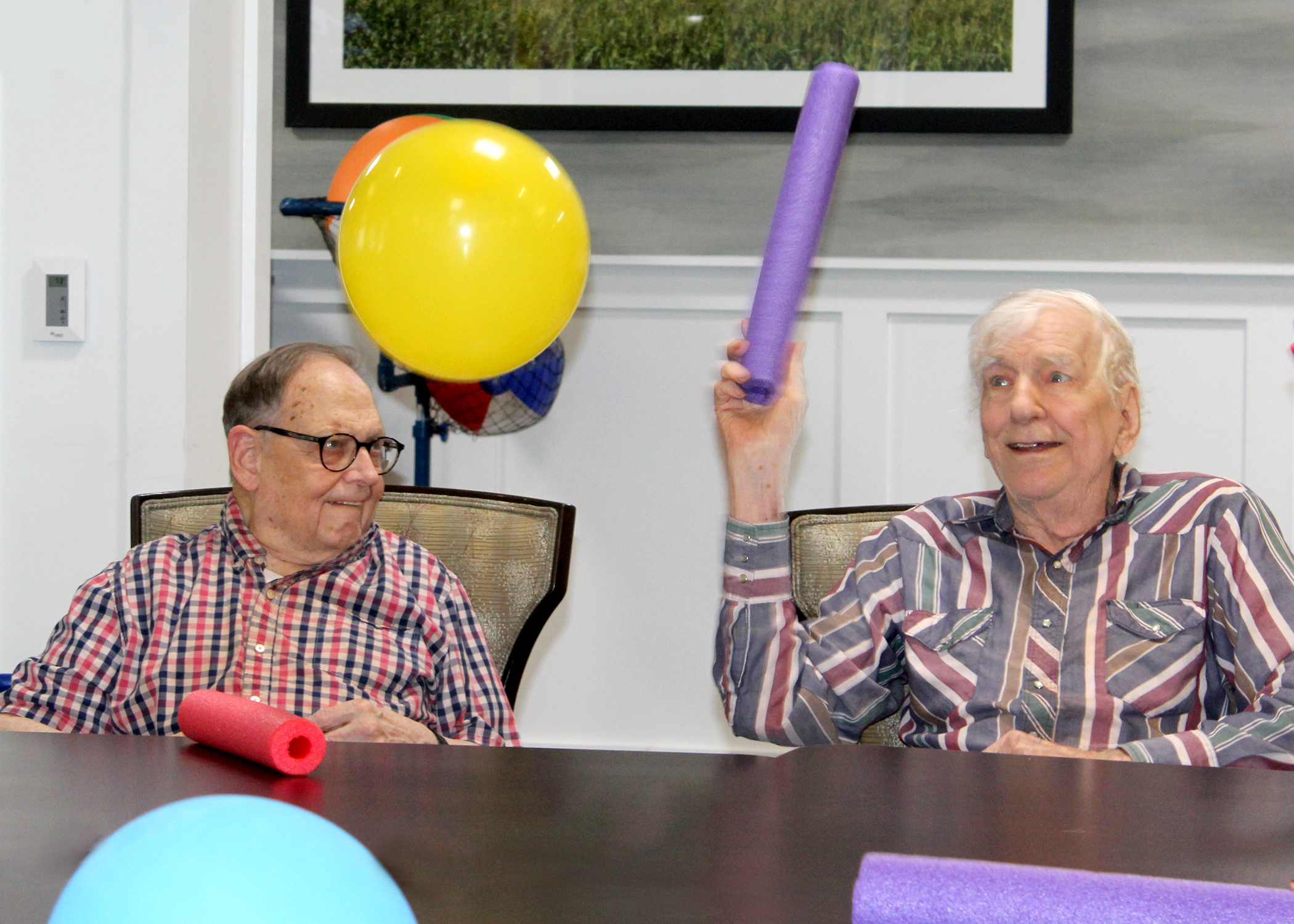 Two male memory care residents playing balloon noodle with colorful balloons in the air
