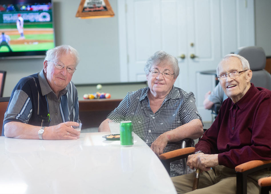 Male and female residents smiling at camera while enjoying a baseball game and snacks in the club
