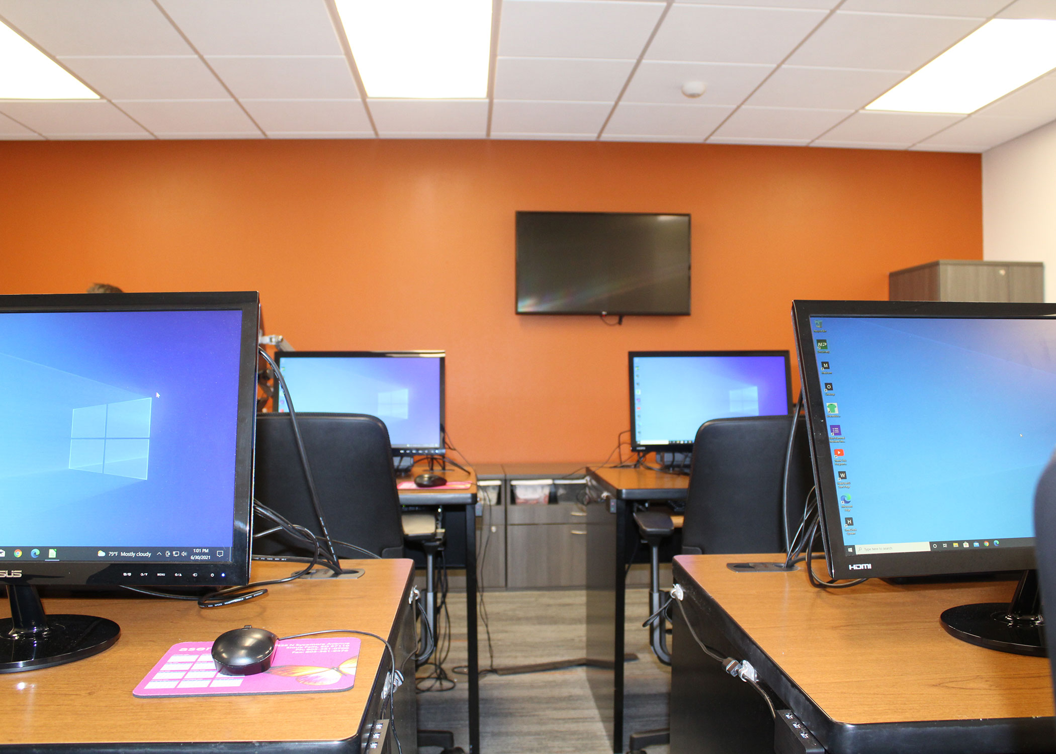 Wilma M. Wagner Computer lab with four stations against a orange wall