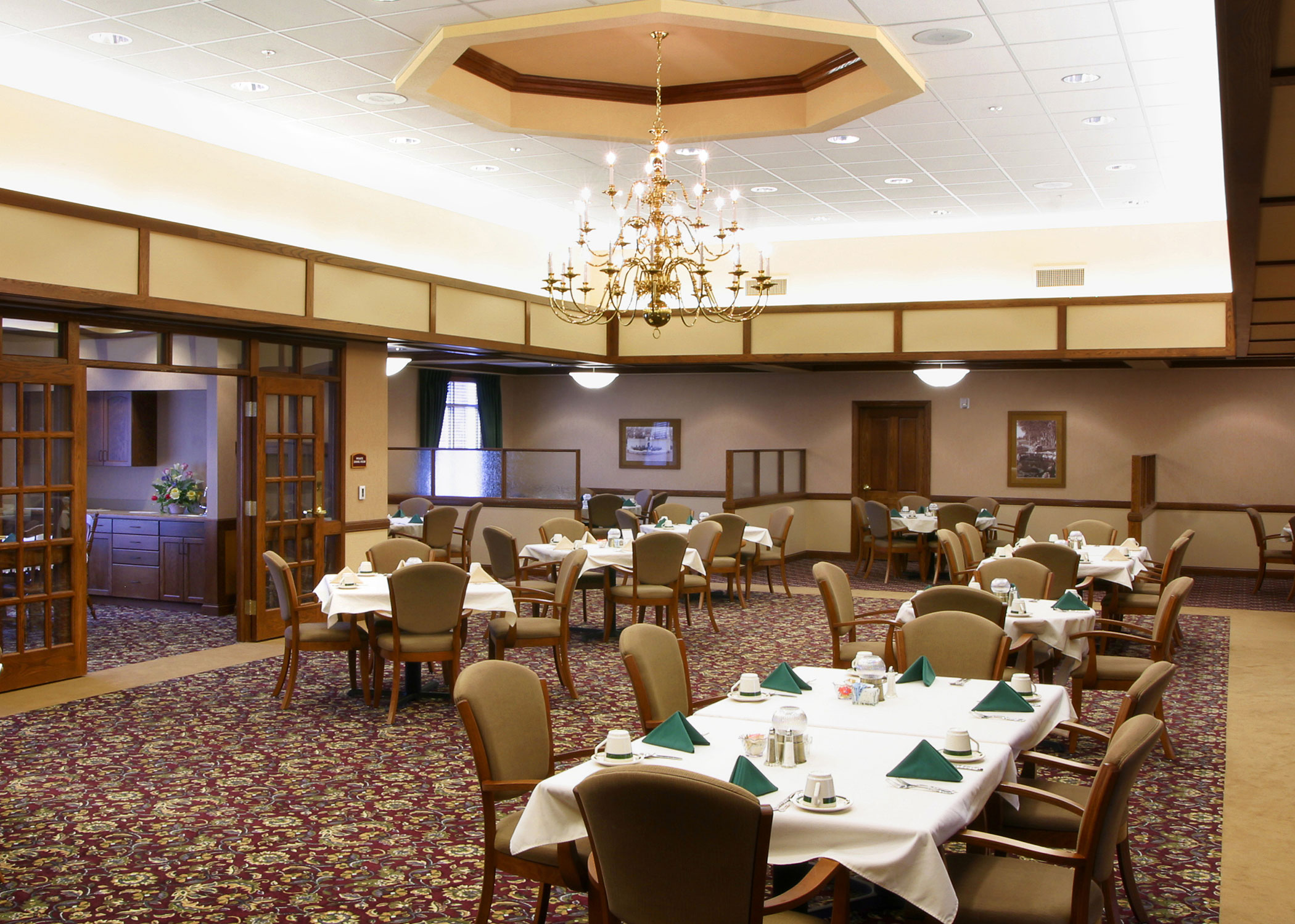 Interior of Covell's Restaurant with a large gold chandelier and set tables with white table cloths, green cloth napkins and coffee cups