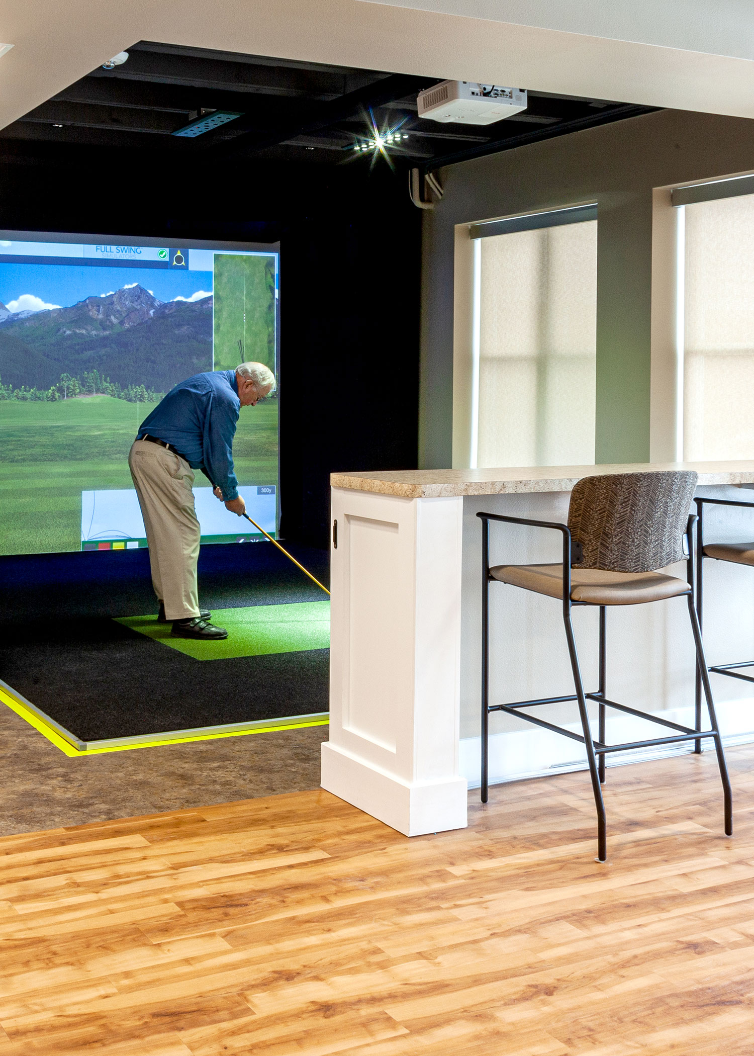 Male resident golfing at the indoor golf simulator
