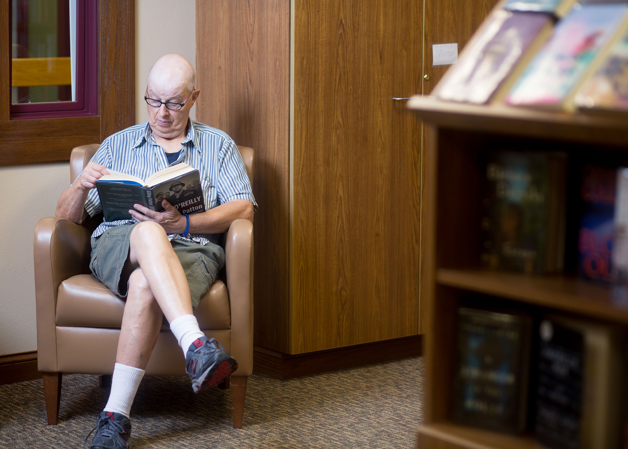 Male resident  with shorts and glasses sitting in a chair at the library reading a book