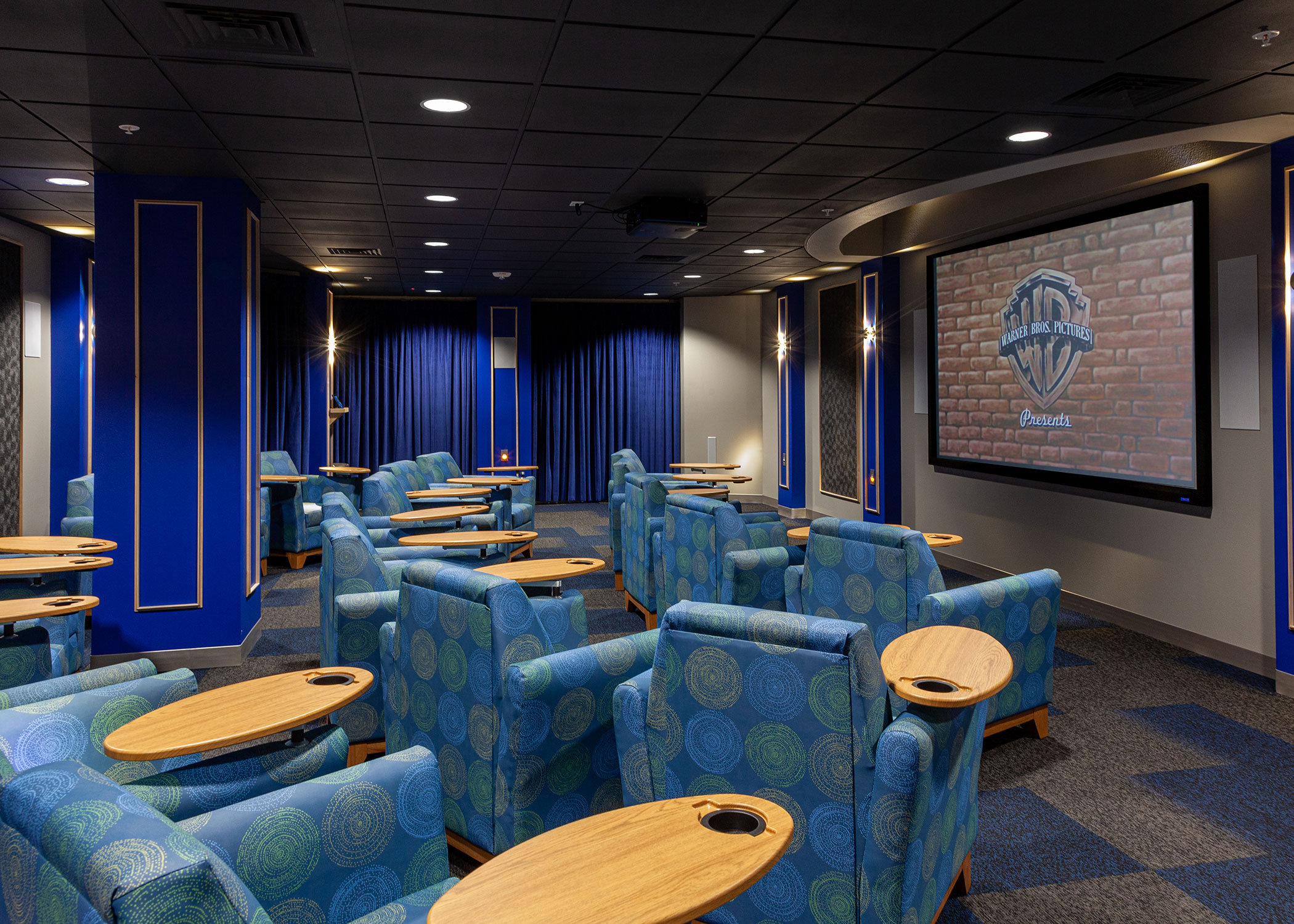 Inside of Warner Movie Theater with blue seat, blue curtains, soft lighting and a Warner Brothers Movie on screen