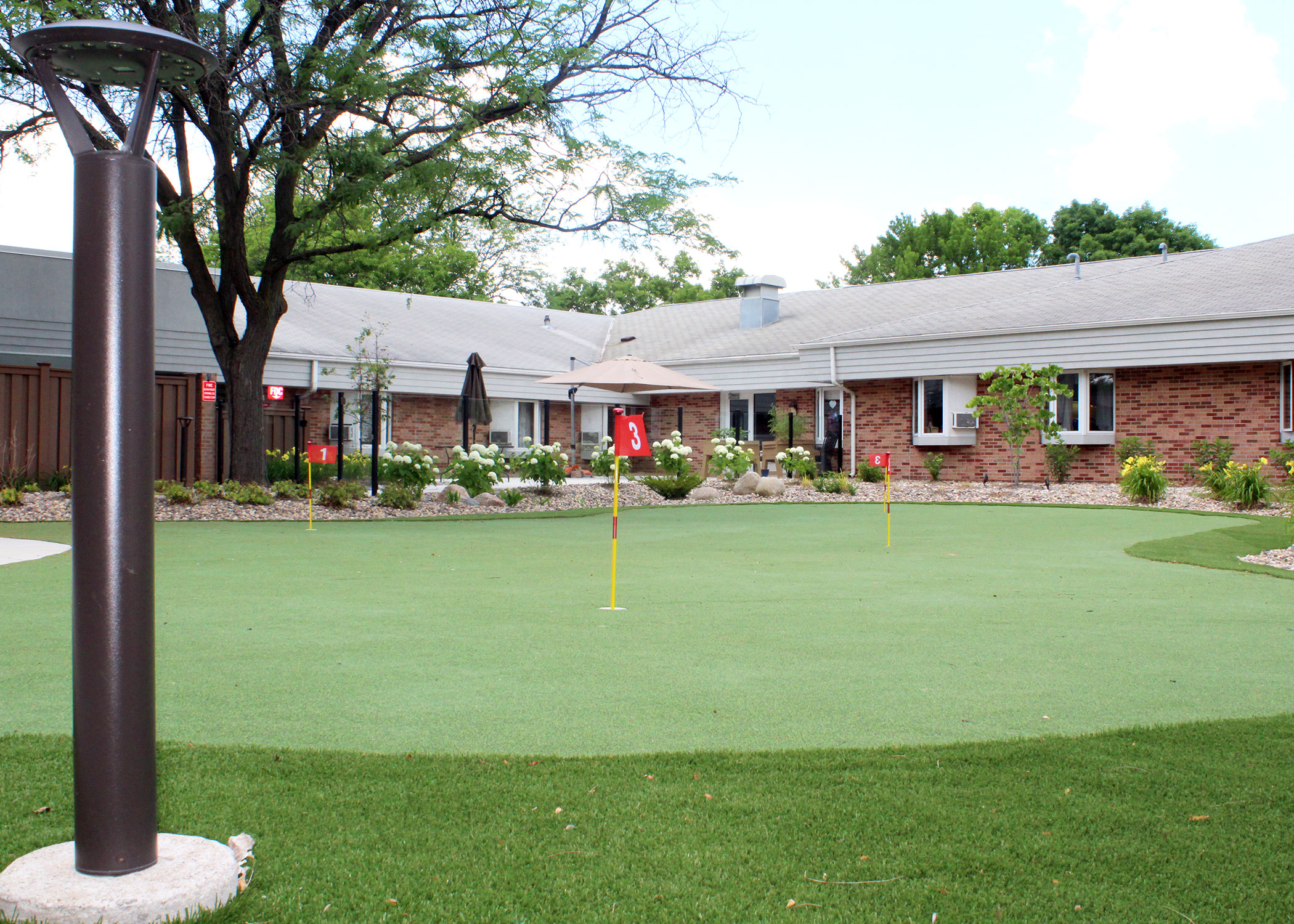 The outdoor putting green nestled in a courtyard with beautiful landscaping