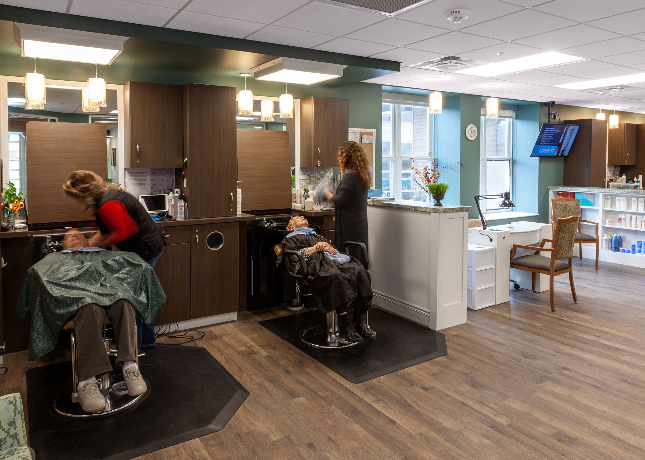 Two female residents getting their hair washed by stylists at the Main Street Salon and Spa