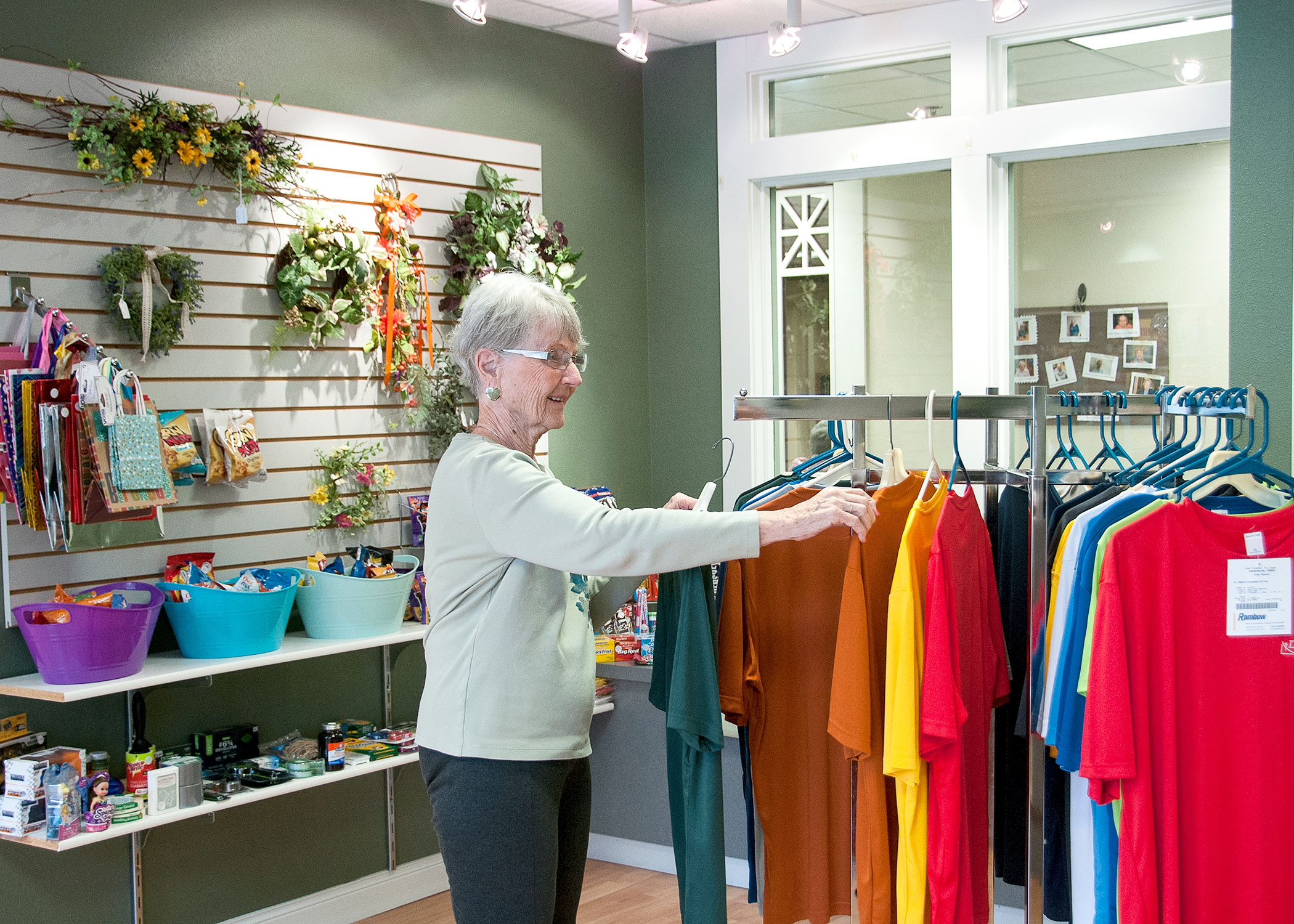 female independent living resident looking at a rack of shirts in the Village Shoppe