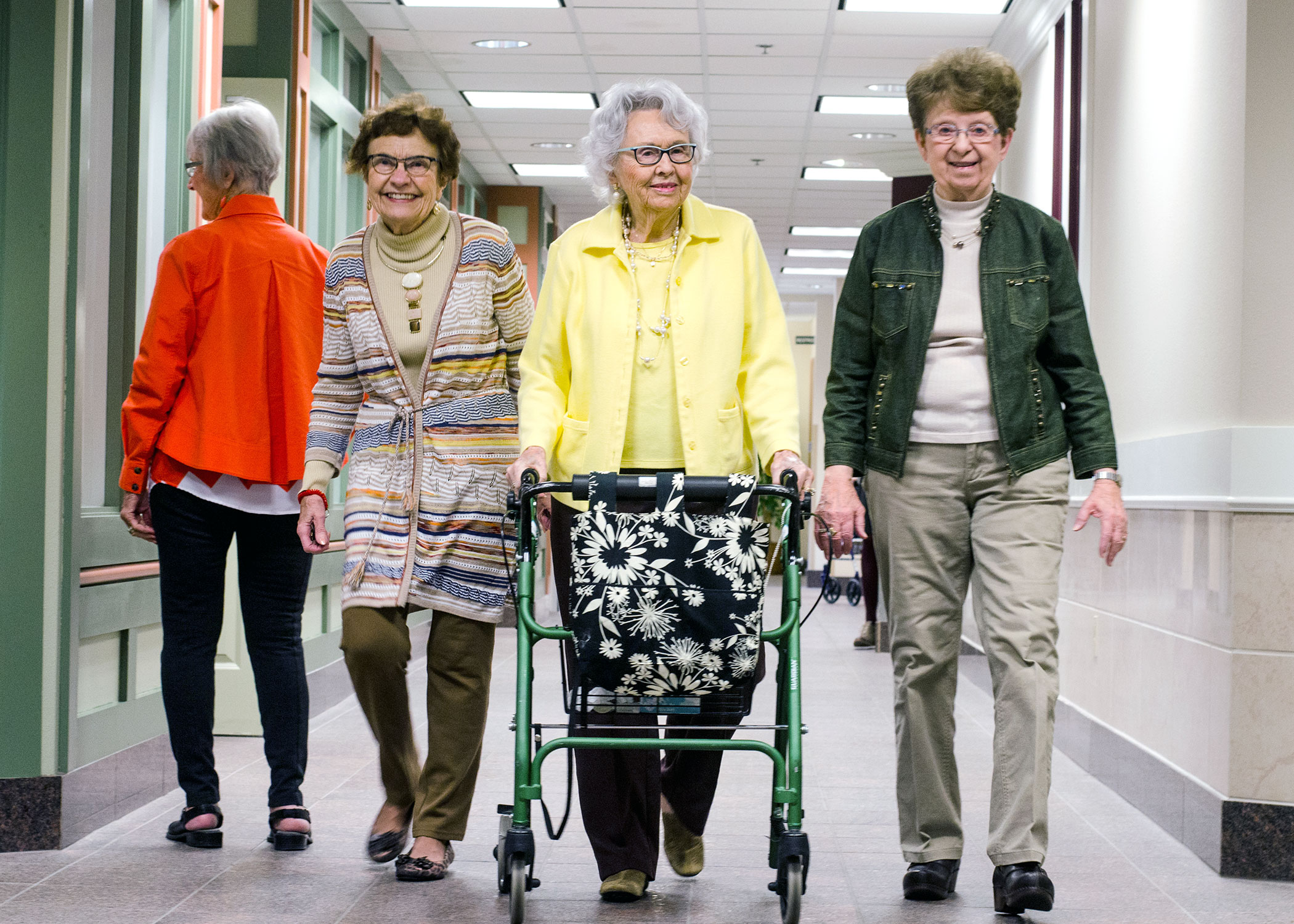 A group of three ladies walking down main street. One is using a walker. Another lady is looking in a window at the Club
