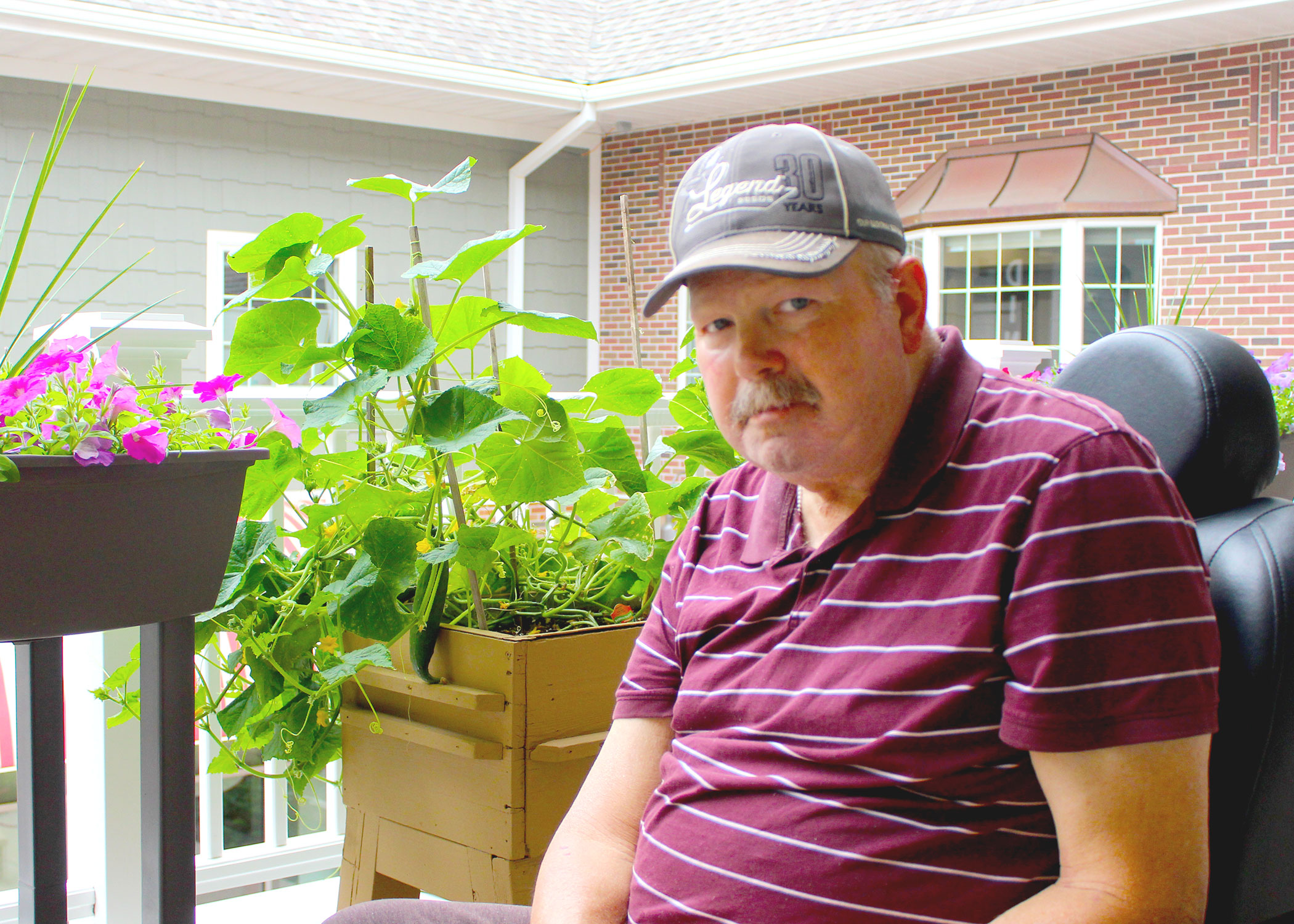 Enhanced Assisted Living Male resident wearing a maroon stripe shirt and gray baseball cap sitting on the porch with garden plants and flowers he is growing