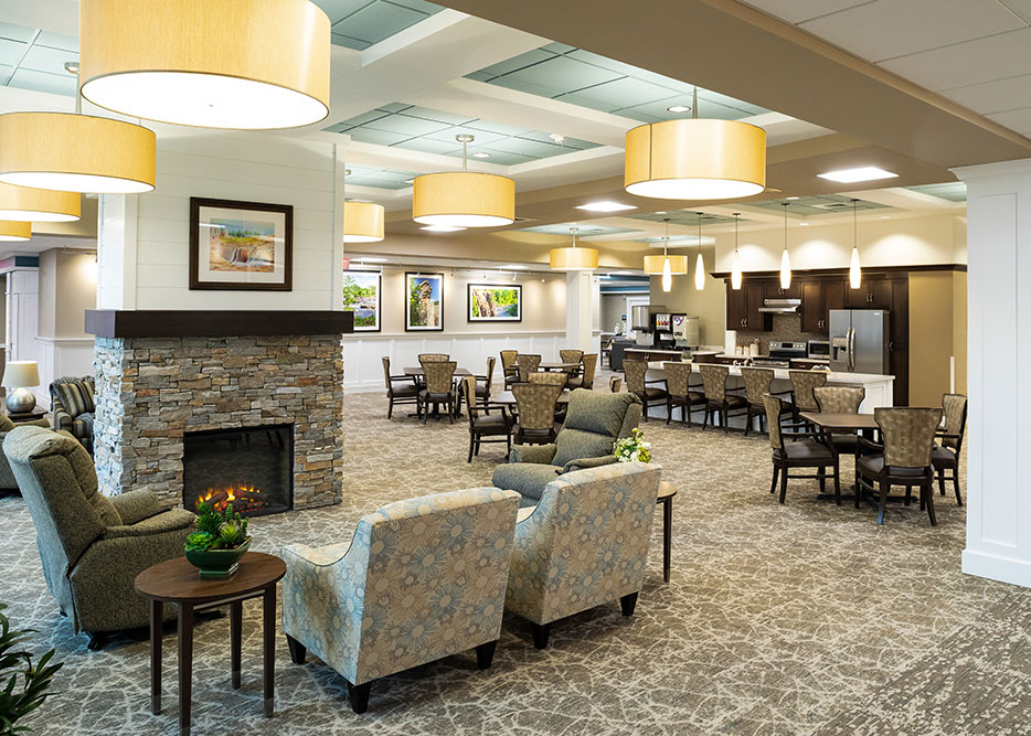 Enhanced Assisted Living and Memory Care open living room and kitchen area with circadian lighting