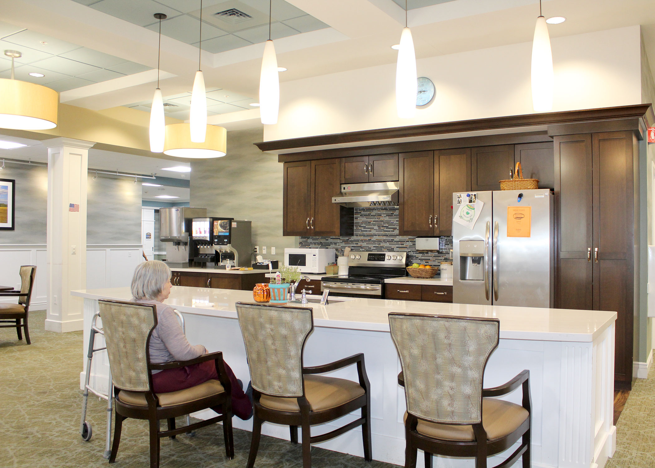 Enhanced Assisted Living and Memory Care Open Kitchen Concept with female resident enjoying a snack at the island