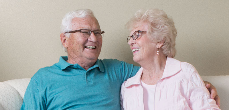 Independent living couple smiles at each other while sitting on a couch